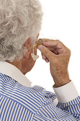 Closeup of a senior  man inserting a hearing aid in her hear.