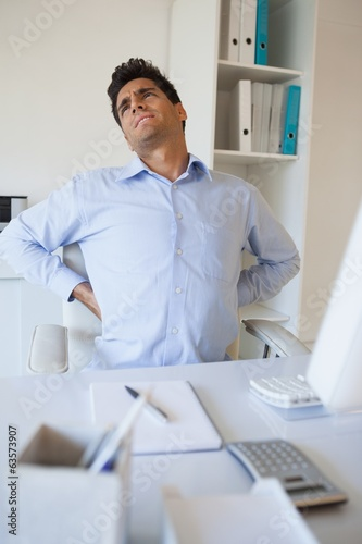 Casual businessman stretching his sore back