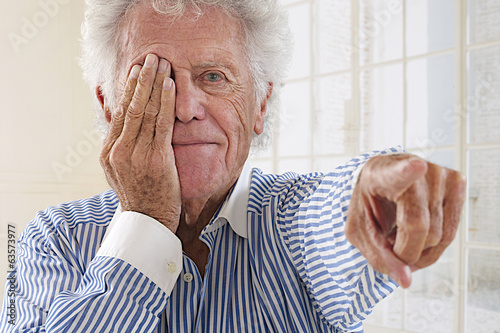 Portrait of an elderly  man taking eyesight test