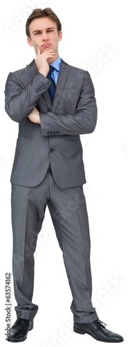 Thinking young businessman in grey suit