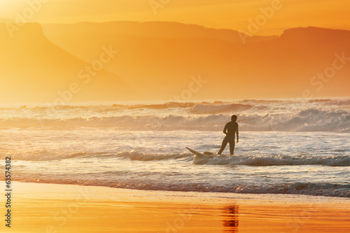 surfer exiting water at sunset