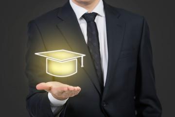 Businessman holding a hologram graduation hat.