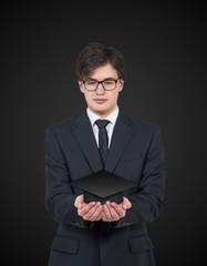 Student holdina a graduation hat. Black background.