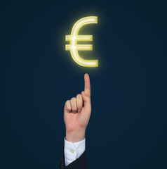 A hand pointing out to Euro sign. Black background.