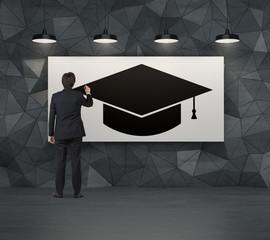 Businessman drawing a graduation hat