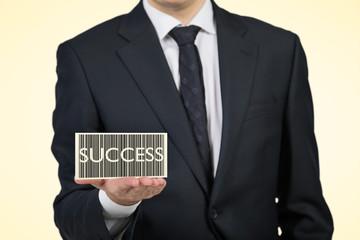 Businessman holding a card 'success'