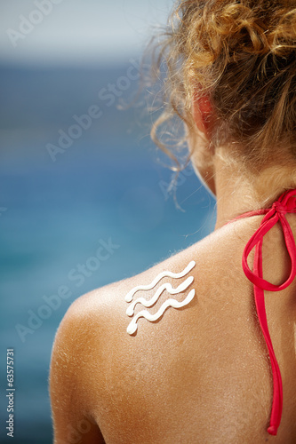 Woman with suntan lotion at the beach in form of a waves