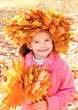 Autumn portrait of smiling little girl in maple wreath