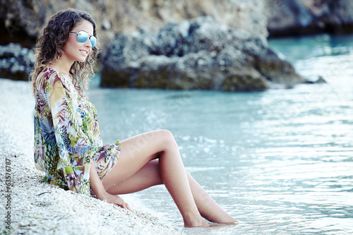 Photo of a beautiful woman in a dress on a adriatic beach