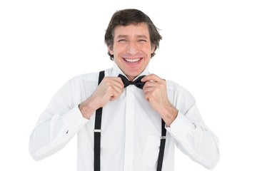 Man adjusting bow tie before wedding