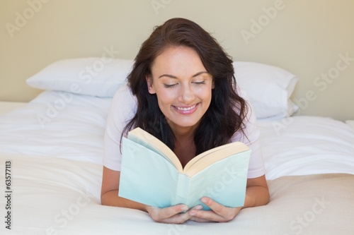 Smiling woman reading book while lying in bed