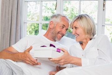 Woman giving mature man a gift box