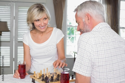 Happy mature couple playing chess