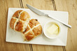 Hot cross bun on white dish