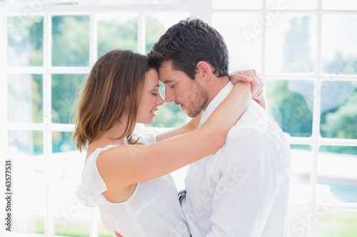 Loving young couple with arms around
