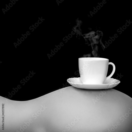 Gray tones photo of cup of coffee on woman's torso