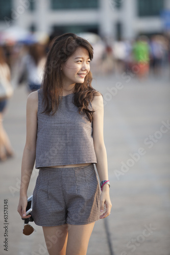 young attractive asian woman walking out door with relaxing and