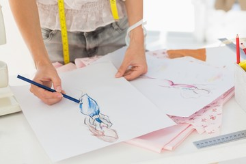 Mid section of a fashion designer working on her designs