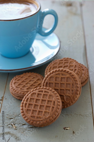 A cup of black coffee and chocolate biscuits