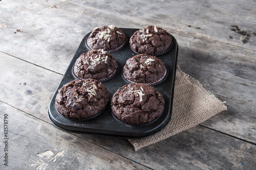 Chocolate cupcakes on a wooden table.