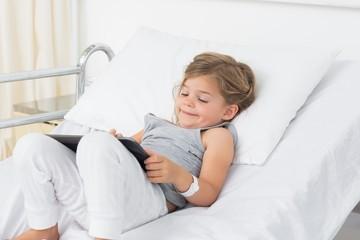 Little sick girl using digital tablet