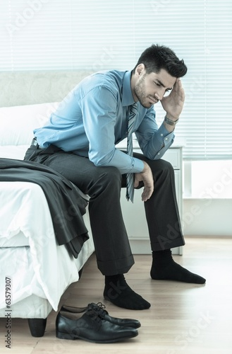Wincing businessman sitting at edge of bed