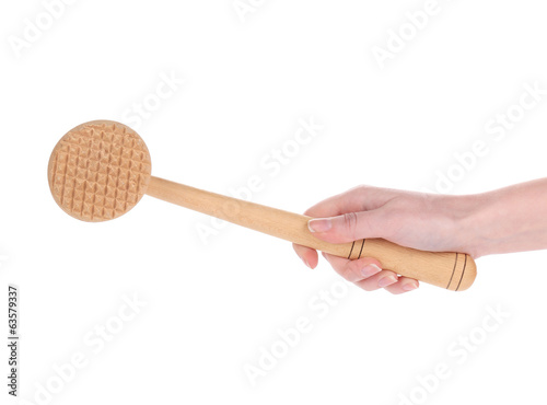 Hand holds wooden meat tenderizer.