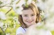 Kleines Mädchen zwischen blühenden Zweigen