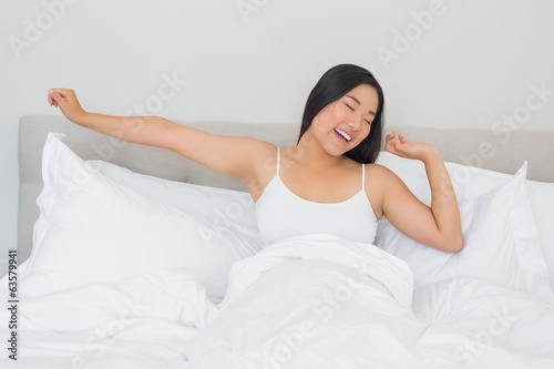 Smiling woman lying in bed stretching in the morning