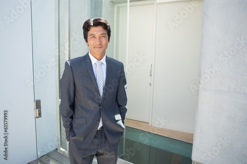 Confident estate agent standing at front door
