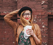 stylish woman holding coffee and hat on brick wall background