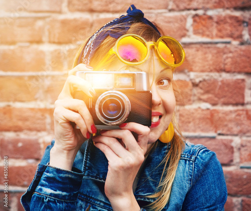 canvas print picture smiling girl with vintage camera taking photo with flash on bric