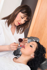 stylist applying makeup to a client in beauty salon