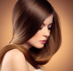 Tender woman with perfect shiny long hair posing in studio