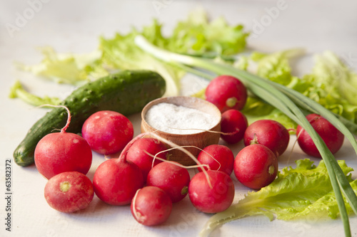 radish, onion, cucumeber, salad leafs and salt on a table