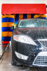 Black car in automatic car wash, rotating blue and yellow brushe
