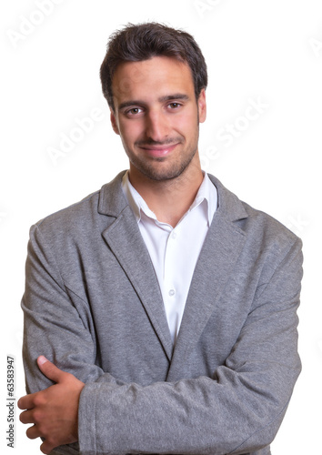 Smiling latin businessman in grey suit with crossed arms