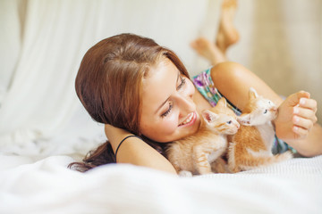 Woman relaxing on a bed with a very cute kitten