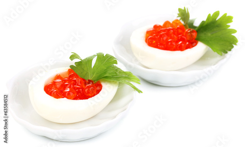 Red caviar in eggs on little white saucers isolated on white