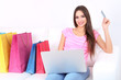 Beautiful young woman holding laptop with shopping bags
