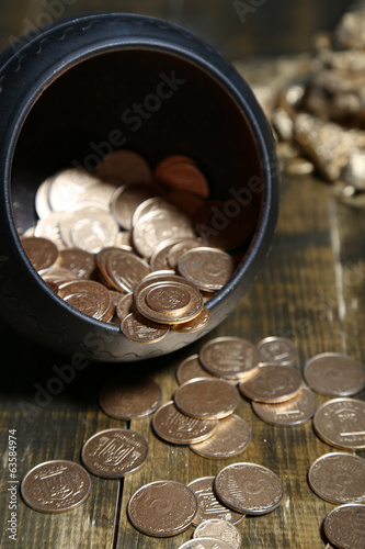 Golden coins falling out from pot, on wooden background