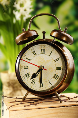 Alarm clock on nature background