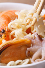 chopsticks keep the Chinese noodles in soup from seafood