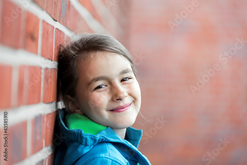 Portrait of a happy little cute girl next to Brick Wall