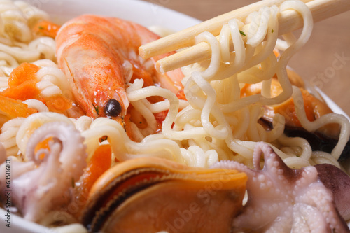 chopsticks hold noodles against soup from seafood