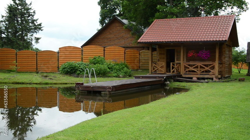 Garden wooden log bath bathhouse sauna near small bridge on pond
