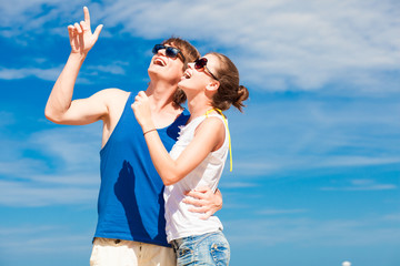 Closeup of happy young couple in sunglasses on beach smiling and