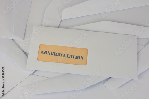 congratulation announcement, white envelope on heap of envelopes