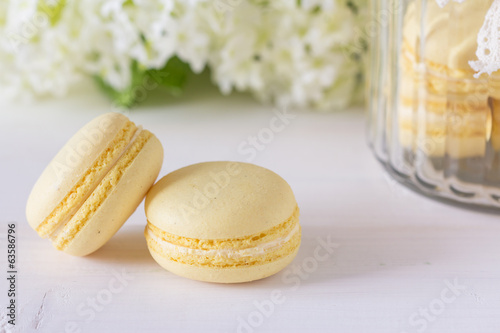 Two macaroons on an ornately set table with elderberry blossoms
