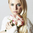 Beautiful Woman with bouquet of Flowers.Blond girl and roses
